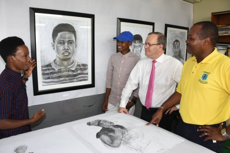 Kirk Cockburn (left) explains the details of his mirror portrait to (L-R) fellow student artiste, Rameesh Ramsay, Alain Carreau, CEO RUBiS Energy Jamaica and Shawn Aarons, Principal Dunoon Technical High School during the InPulse Art Project open studio exhibit on Friday, November 25.