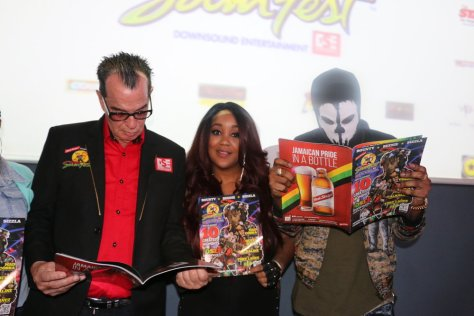 Josef Bogdanovich CEO of Downsound Entertainment and organiser of Reggae Sumfest (l) stands with Tifa and Tommy Lee as they take a look at the Reggae Sumfest 25 magazine at the Montego Bay staging of the festival's launch held at the Iberostar Rose Hall Suites on Thursday May 18.